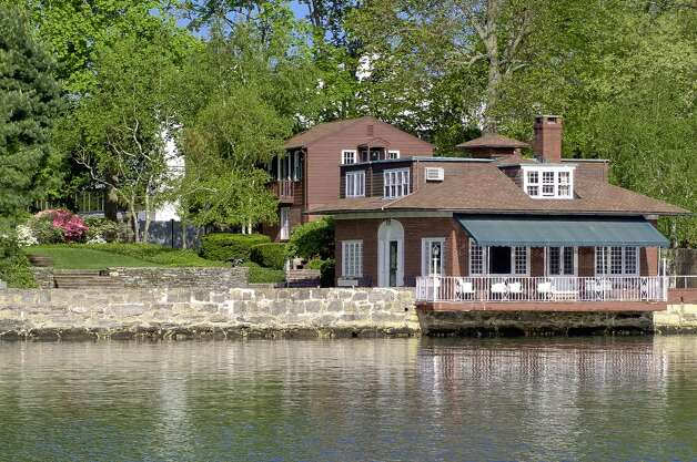A waterfront gem on Steamboat Road sits just above Smith Cove looking out to L.I. Sound and beyond. Sheltered within stone-walled gardens are the one-time carriage house and two-car garage with studio and bath above. A cobblestone courtyard leads to green terraced lawns that run down to the water, and there's a terrace that sits above the cove waters and stone-floored patios and a boat launch with a hoist. The former carriage house, crafted of brick and shingle, has three bedrooms and three baths.