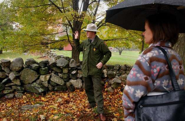Cliff Laube, a park ranger at Weir Farm, talks about the throne stone walls built by farm hands in the 1700s as Norwalk resident Carolyn Callan listens. Stone wall walking tours take place on Sundays at the farm. Kerry Sherck/Staff photo