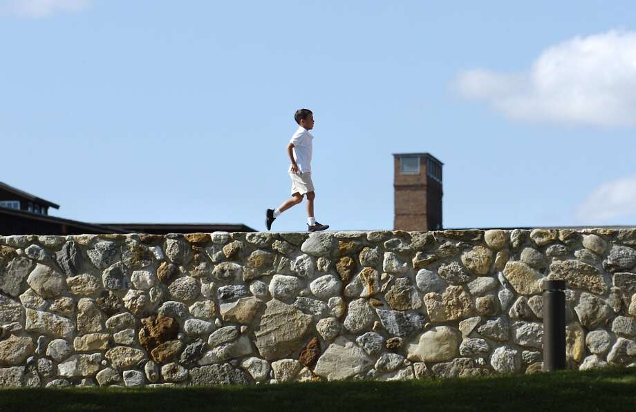 J.J. Vonoiste,8, a 3rd grader at Brunswick School in Greenwich, runs atop a stone wall at the Brunswick School's  King Street campus late Wednesdy afternoon.  Vonoiste was playing with schoolmates and it was his turn to run the wall.  Bob Luckey/Staff PhotoOIn Top of the world.