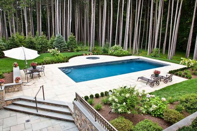 The terraced stone patio features an in-ground pool, grill, several stone walls and gardens at this home on Pan Handle Lane in Westport