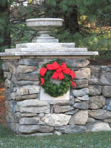 A wreath hangs on a stone wall on New Canaan's Dan's highway.