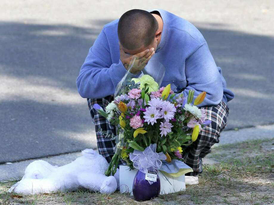 Jeremy Bush places flowers and a stuffed animal at a makeshift memorial in front of a home where a sinkhole opened up underneath a bedroom late Thursday evening and swallowed his brother Jeffrey in Seffner, Fla. on Saturday, March 2, 2013.   Jeffrey Bush, 37, was in his bedroom Thursday night when the earth opened and took him and everything else in his room. Five other people were in the house but managed to escape unharmed. Bush's brother jumped into the hole to try to help, but he had to be rescued himself by a sheriff's deputy. Photo: Chris O'Meara, Associated Press / AP