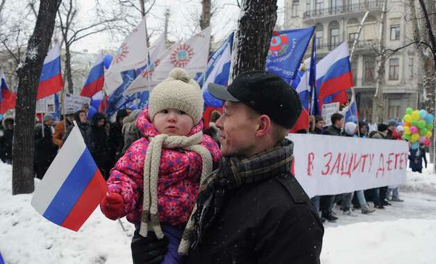 "A man walks with his child, as activists from pro-Kremlin children's advocacy groups march through Moscow on March 2, 2013 to call on authorities to ban all foreign adoptions and demand the return of an adopted boy whose brother died in Texas. The banner reads ""The March for Protection of the Children"". Photo: ALEXANDER NEMENOV, AFP/Getty Images / AFP"