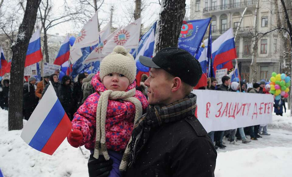 A man walks with his child, as activists from pro-Kremlin children's advocacy groups march through M