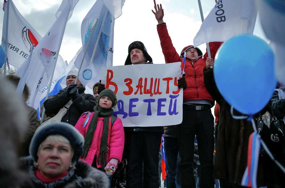 "A demonstrators holds a poster reading ""In Defense of Children"" during a massive rally to back the ban on U.S. adoptions of Russian children in Moscow, Saturday, March 2, 2013. Russia voiced strong skepticism Saturday about the U.S. autopsy on Max Shatto, a 3-year-old adopted Russian boy in Texas and demanded further investigation as thousands rallied in Moscow to support the Kremlin ban on U.S. adoptions of Russian children. Photo: Alexander Zemlianichenko, Associated Press / AP"