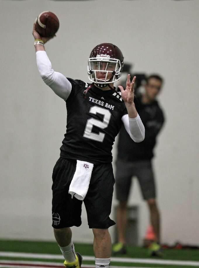 The cameras and the spotlight are on Texas A&M quarterback Johnny  Manziel after his Heisman Trophy win and the Aggies' top-five finish  last season. (Photo: Eric Christian Smith/For the Houston Chronicle) Photo: Eric Christian Smith, For The Chronicle