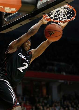 Cincinnati forward Titus Rubles (2) dunks the ball against Connecticut during the first half of an NCAA college basketball game, Saturday, March 2, 2013, in Cincinnati. (AP Photo/David Kohl)