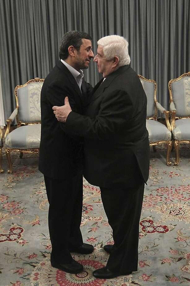 Iranian President Mahmoud Ahmadinejad, left, welcomes Syrian Foreign Minister Walid al-Moallem, for their meeting, in Tehran, Iran, Saturday, March 2, 2013. (AP Photo/Fars News Agency, Mahdi Marizad) Photo: Mahdi Marizad, Associated Press