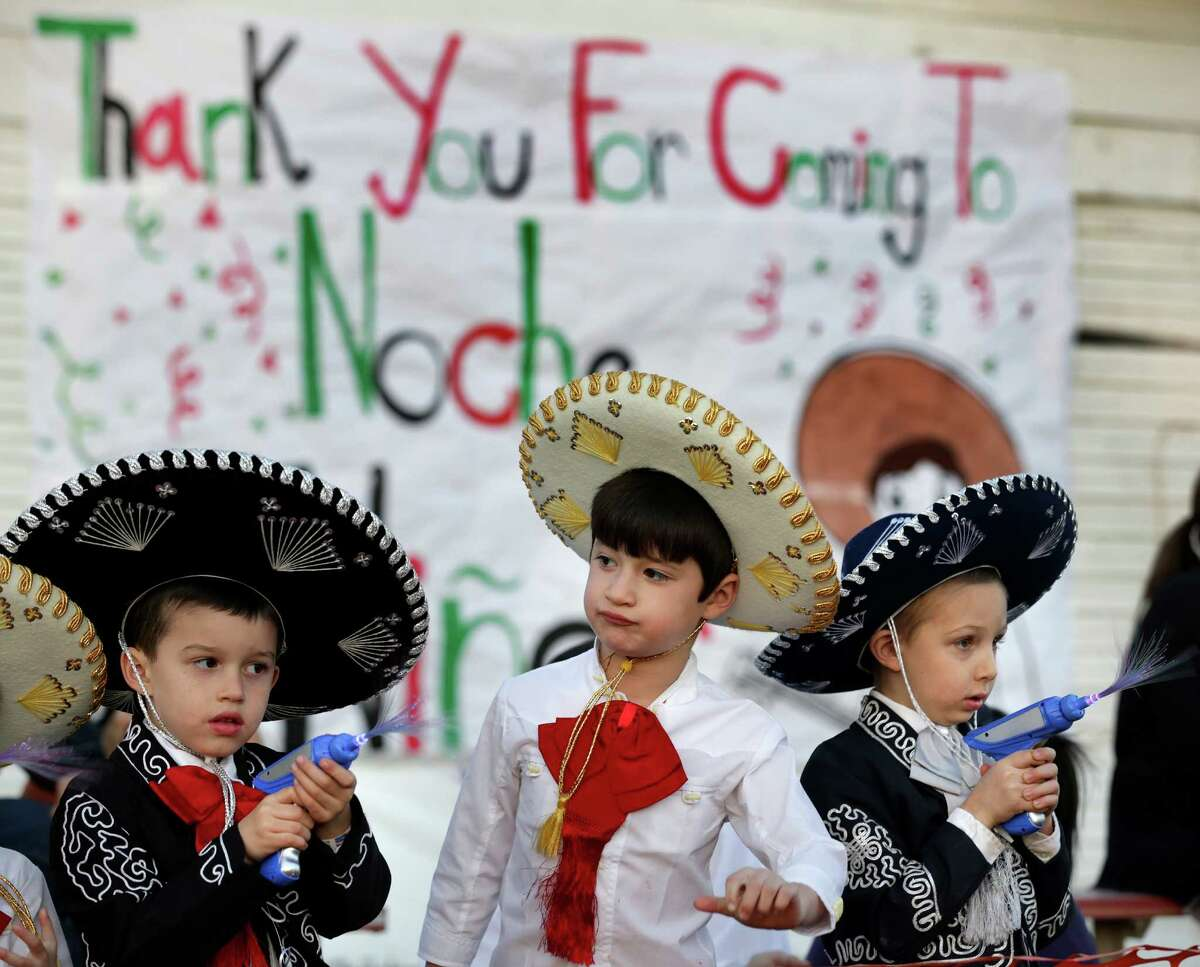 Three amigos Joseph Rosales, left to right, Christopher Prettyman, and William Rosales, decked out in their best Charro outfits, play with their light toys at the Illuminated Parade during Charro Days Fiesta in Brownsville, TX on Friday, March 1, 2013 on Elizabeth St.