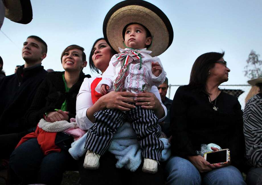 Alfredo Coronado has a high pearch on his mother Delia Sandoval's lap at The Illuminated Parade during Charro Days Fiesta in Brownsville, TX on Friday, March 1, 2013 on Elizabeth St. Photo: Bob Owen, San Antonio Express-News / ©2013 San Antonio Express-News