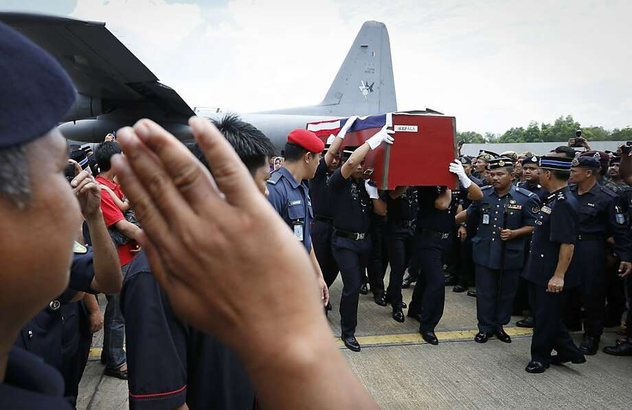 Malaysian police officers salute the coffins of two commandos who were killed during the standoff with 200 members of a Filipino clan who landed and occupied a village in Malaysia. Photo: Vincent Thian, Associated Press
