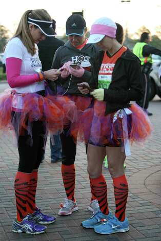 (Left to right) Lisa Overby, Carla Reid and Kassie Leincester check text messages before the running of The Woodlands Marathon, Saturday, March 2, 2013 in The Woodlands.(Photo: Eric Christian Smith: For the Houston Chronicle) Photo: Eric Christian Smith, For The Chronicle