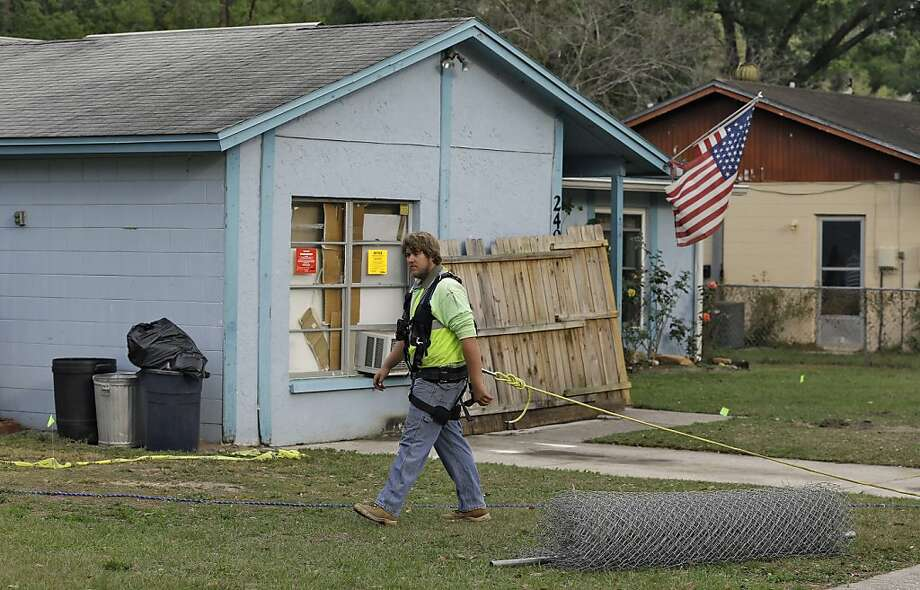 An engineer tethered with a safety line walks in front of a home where a sinkhole opened up and swallowed a man in Seffner, Fla. Officials are trying to learn the extent of the danger. Photo: Chris O'Meara, Associated Press