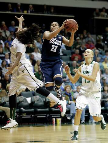 Connecticut forward Kaleena Mosqueda-Lewis (23) goes to the basket between South Florida forward Tiffany Conner (4) and guard Inga Orekhova (13) during the second half of an NCAA women's college basketball game Saturday, March 2, 2013, in Tampa, Fla. Connecticut won the game 85-51. (AP Photo/Chris O'Meara) Photo: Chris O'Meara, Associated Press / AP