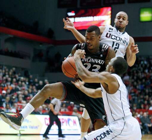 Cincinnati guard Sean Kilpatrick (23) goes for a rebound against Connecticut guards R.J. Evans (12) and Ryan Boatright (11) during the second half of an NCAA college basketball game, Saturday, March 2, 2013, in Cincinnati. Cincinnati won 61-56. (AP Photo/David Kohl) Photo: David Kohl, Associated Press / FR51830 AP
