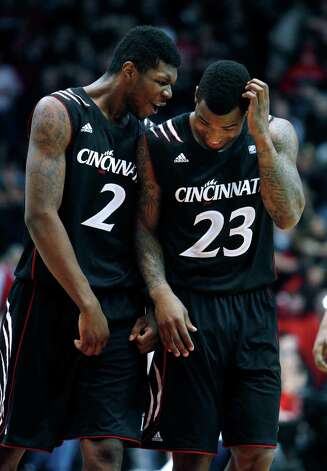 Cincinnati forward Titus Rubles (2) and guard Sean Kilpatrick (23) talk with each other during the final seconds of an NCAA college basketball game against Connecticut, Saturday, March 2, 2013, in Cincinnati. Cincinnati won 61-56. (AP Photo/David Kohl) Photo: David Kohl, Associated Press / FR51830 AP