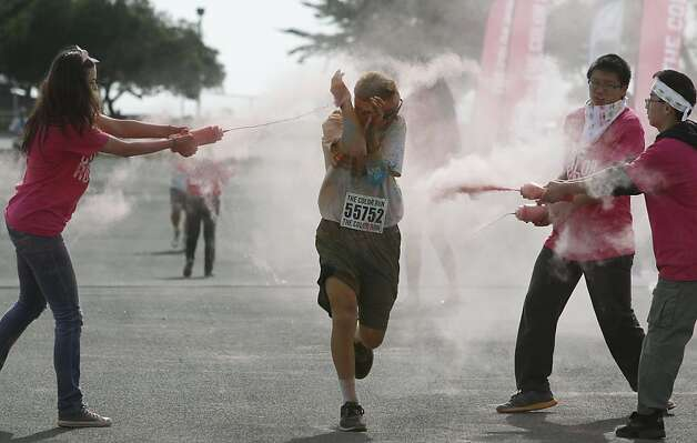 Volunteers squirt dyed cornstarch on runners participating in the Color Run 5K near Candlestick Park in San Francisco. Photo: Paul Chinn, The Chronicle