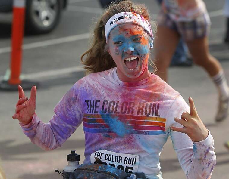 A runner celebrates as she nears the end of the Color Run. Part of the race proceeds go to the parks