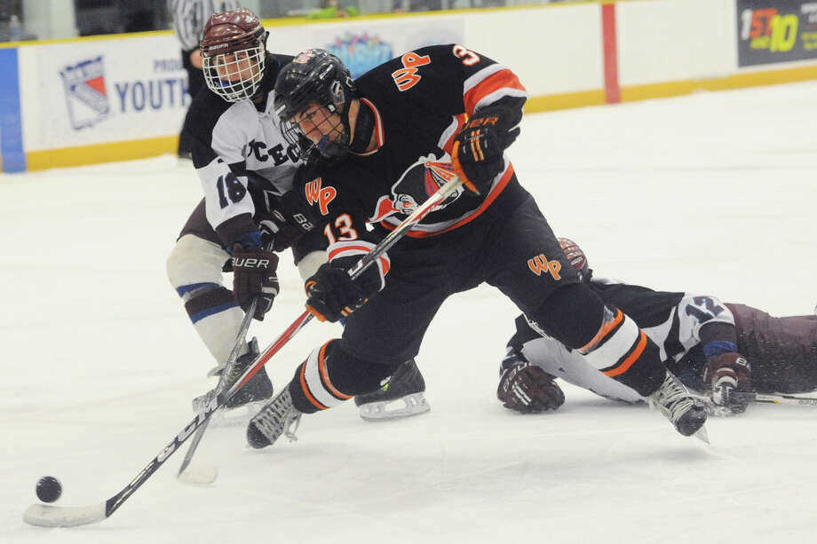 Watertown/Pomperaug's Kyle Block (13) shoots at the goal defended by Brookfield/Bethel/Danbury's William Hunt (18) and Jake Maddox (12) during Watertown/Pomperaug's 5-1 win over Brookfield/Bethel/Danbury in the boys SWC hockey championship at Danbury Arena Saturday, March 2, 2013. Photo: Tyler Sizemore / The News-Times