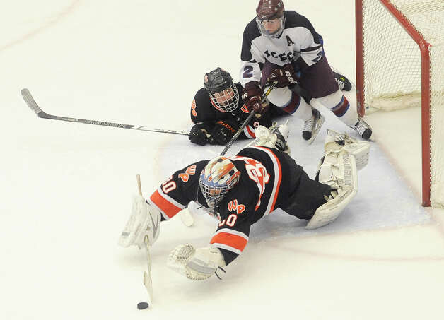 Watertown/Pomperaug goalie Trevor St. Onge dives after the puck in front of his teammate Bobby Narciso and Brookfield/Bethel/Danbury's Matthew Hallock during Watertown/Pomperaug's 5-1 win over Brookfield/Bethel/Danbury in the boys SWC hockey championship at Danbury Arena Saturday, March 2, 2013.  St. Onge was the tournament MVP. Photo: Tyler Sizemore / The News-Times