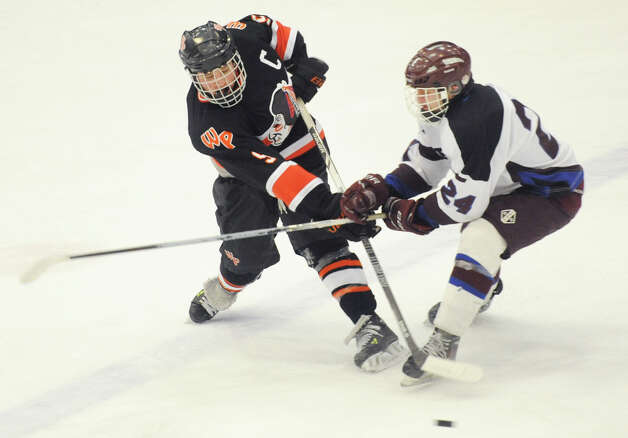 Watertown/Pomperaug's Bobby Narciso, left, shoots defended by Brookfield/Bethel/Danbury's Jonathan Leonard during Watertown/Pomperaug's 5-1 win over Brookfield/Bethel/Danbury in the boys SWC hockey championship at Danbury Arena Saturday, March 2, 2013. Photo: Tyler Sizemore / The News-Times