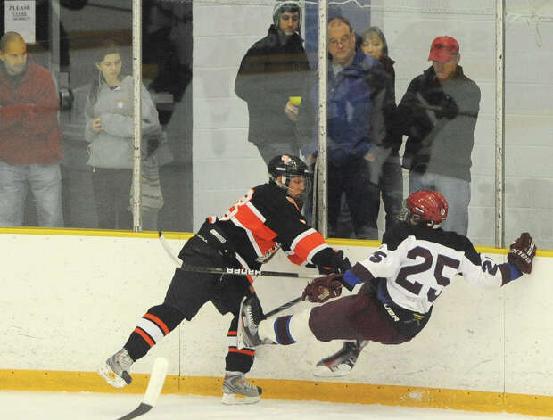 Watertown/Pomperaug's Dave Hughes, left, checks Brookfield/Bethel/Danbury's Daivon Ruggiero during Watertown/Pomperaug's 5-1 win over Brookfield/Bethel/Danbury in the boys SWC hockey championship at Danbury Arena Saturday, March 2, 2013. Photo: Tyler Sizemore / The News-Times