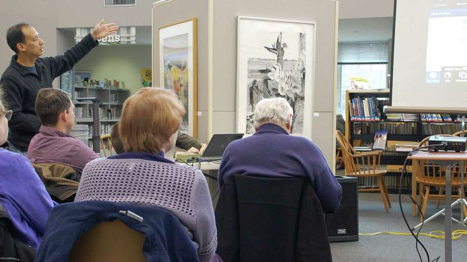 """Norman Tsang of Westport shares an app called """"Where's Our School Bus?,"""" which enables parents and students to keep track of school buses. He and others discussed apps for electronic devices Saturday at the Westport Public Library's """"App Slam.""""  WESTPORT NEWS, CT 3/2/13 Photo: Jarret Liotta / Westport News contributed"""
