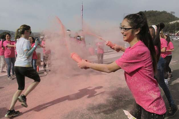 Khaliuna Bayasgalan squirts pink powder on participants nearing the finish line of the Color Run 5K run at Candlestick Park in San Francisco, Calif. on Saturday, March 2, 2013. Photo: Paul Chinn, The Chronicle