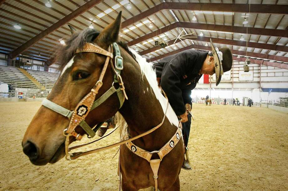 Ramona Jefferson adjusts her saddle as she warms up her bay tobiano pinto paint horse named Bianca during the Black Professional Cowboys & Cowgirls Association's 14th annual Heritage Day, Saturday, March 2, 2013, at the Humble Civic Arena in Humble. Photo: Nick De La Torre, Chronicle / © 2013 Houston Chronicle