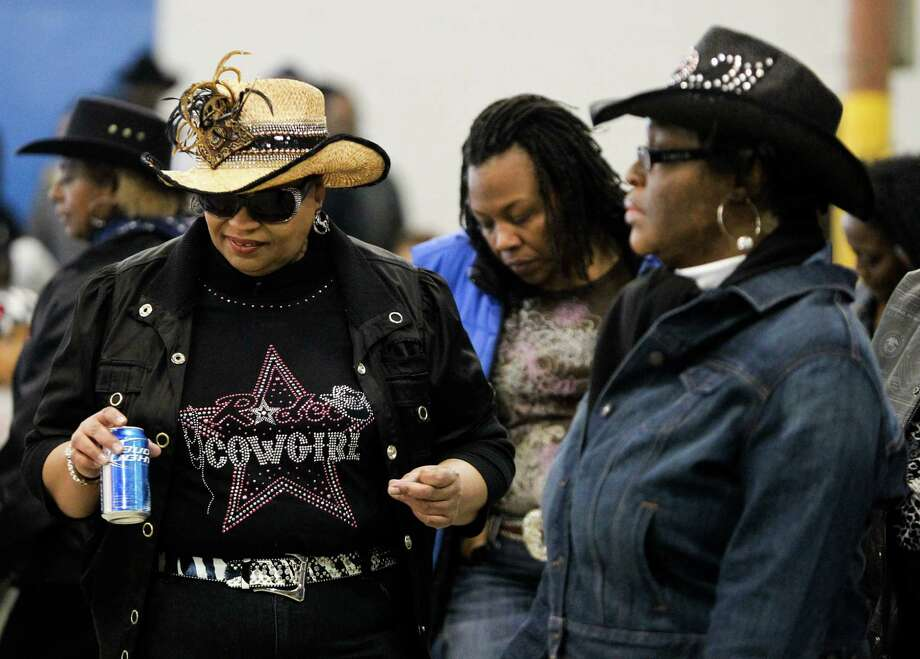 Penny Judge, of Barrett Station, line dances with a group of women during the Black Professional Cowboys & Cowgirls Association's 14th annual Heritage Day, Saturday, March 2, 2013, at the Humble Civic Arena in Humble. Photo: Nick De La Torre, Chronicle / © 2013 Houston Chronicle