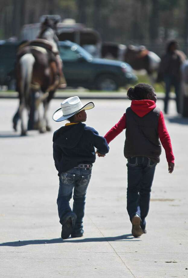 Brailyn Carter, 5, walks with her friend Cheyenne Williams, 8, to meet up with her parents during the Black Professional Cowboys & Cowgirls Association's 14th annual Heritage Day, Saturday, March 2, 2013, at the Humble Civic Arena in Humble. Photo: Nick De La Torre, Chronicle / © 2013 Houston Chronicle