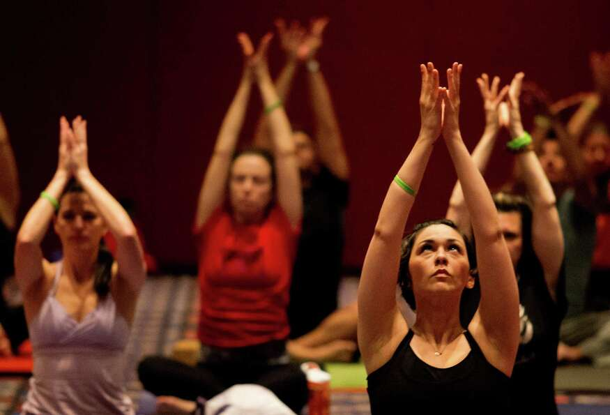 Participants perform yoga techniques during the 2013 Yoga Conference held at the George R. Brown Con