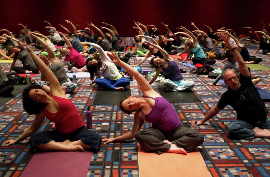 Participants perform yoga techniques during the 2013 Yoga Conference. Photo: J. Patric Schneider, For The Chronicle / © 2013 Houston Chronicle
