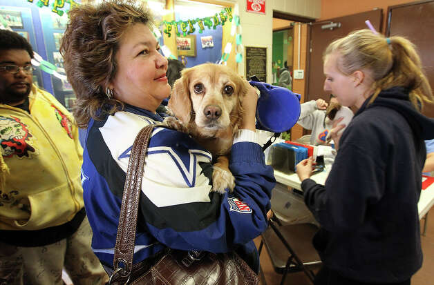 "Pet owner Rosemary Gonzales holds onto her dog, Chyanne, while checking in to be admitted for a spaying procedure at SNIPSA's The Big Fix free spay and neuter clinic at Miller's Pond Community Center on Saturday, Mar. 2,  2013. Over 250 pets were taken in at the clinic that was co-sponsored by the city and by SNIPSA. Veterinarians, vet techs and volunteers converted a gym into a make-shift animal surgical hospital taking in cats and dogs from the area. Veterinarians Shannon and Bob Espy started the program in 2005 in San Antonio. More clinics are planned for the year and pet owners can find information from SNIPSA.org or through the city's Animal Care Services website. The next clinic is planned for April and July according to Espy. SNIPSA's mission is to ""rescue, rehabilitate and re-home adoptable animals"" and ""encourage responsibility within the pet owning population"" according to the website. Photo: Kin Man Hui, San Antonio Express-News / © 2012 San Antonio Express-News"