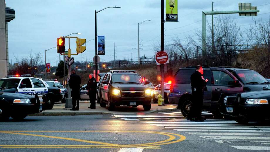 Police officers work at the scene where a pursuit of a shoplifting suspect ended at the intersection of Atlantic and North State Streets in Stamford, Conn., on Saturday, March 2, 2013. Photo: Lindsay Perry / Stamford Advocate