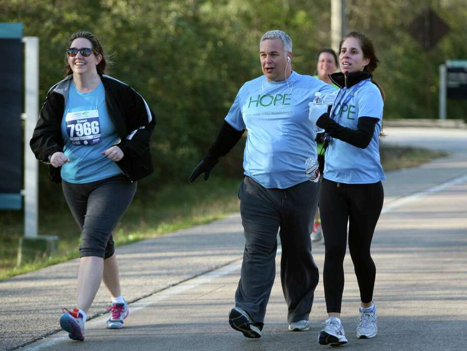 Gladys Guzman jokingly helps husband Xavier Gomez to the finish line of the 5K run during The Woodlands Marathon, Saturday, March 2, 2013 in The Woodlands. Photo: Eric Christian Smith, For The Chronicle
