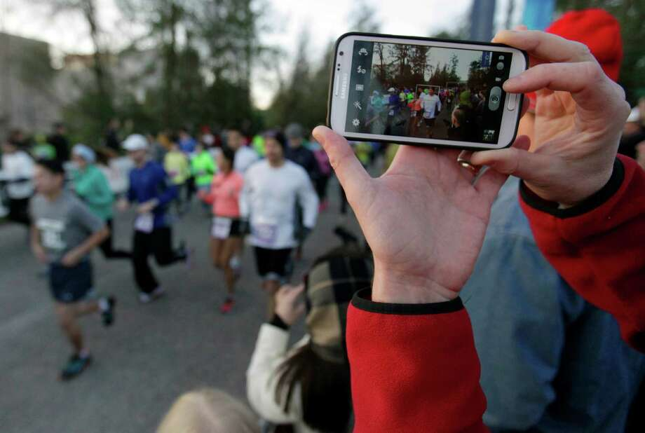 A spectator's camera records video of the beginning of The Woodlands Marathon, Saturday, March 2, 2013 in The Woodlands. Photo: Eric Christian Smith, For The Chronicle