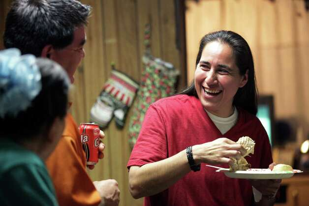 Anna Vasquez, right, enjoys a laugh with her brother David Vasquez and her mother Maria Vasquez over a plate of turkey dinner as they celebrate her first Thanksgivings after being released on parole, Thursday, Nov. 22, 2012. Photo: Bob Owen, San Antonio Express-News / © 2012 San Antonio Express-News