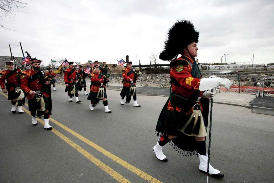 The Staten Island Pipes and Drum band marches in the Queens County St. Patrick's Day Parade in the Rockaway section of New York, Saturday, March 2, 2013. The ocean side community was devastated by flooding and fire during Superstorm Sandy. Behind them is rubble left over from a fire that burned a number of stores in Rockaway Park. Photo: Mark Lennihan, Associated Press / AP