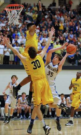 Geoerge King, top, and Paul Derkowski (30) of Brennan defend as Wes Miller of Alamo Heights attempts to shoot during the boys basketball Region iV-4A final at Littleton Gym on Saturday, March 2, 2013. Photo: Billy Calzada, Express-News / San Antonio Express-News