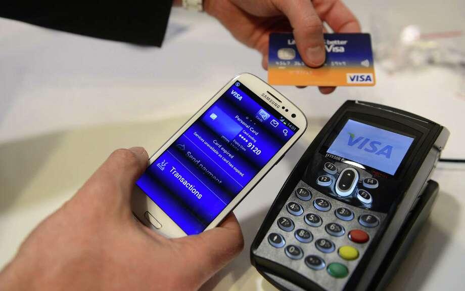 A man uses the NFC payment Visa system. Photo: Manu Fernandez / Associated Press