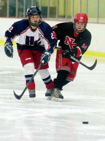 Hall-Conard's Bailey Amenabar, left, and New Canaan's Madzie Carroll, right, compete for control of the puck during Saturday's girls hockey state championship game at Terry Connors Rink in Stamford, Conn., on March 2, 2013. Photo: Lindsay Perry / Stamford Advocate