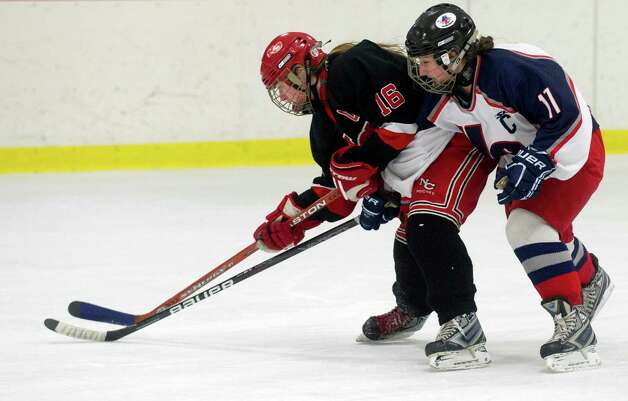 New Canaan's Corbett Ripley, left, and Hall-Conard's Rachel Arnonow, right, compete for control of the puck during Saturday's girls hockey state championship game at Terry Connors Rink in Stamford, Conn., on March 2, 2013. Photo: Lindsay Perry / Stamford Advocate