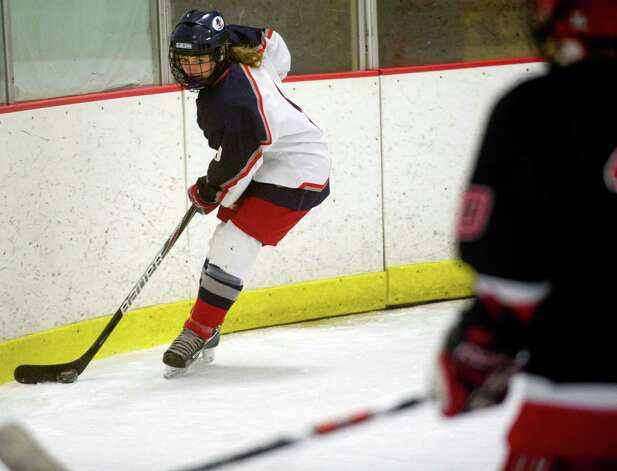 Hall-Conard's Caroline Kuzoin controls the puck during Saturday's girls hockey state championship game against New Canaan at Terry Connors Rink in Stamford, Conn., on March 2, 2013. Photo: Lindsay Perry / Stamford Advocate