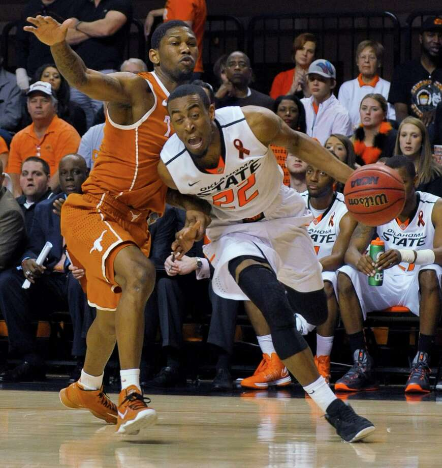 Oklahoma State guard Markel Brown, right, drives past Texas guard Julien Lewis during the second half of an NCAA college basketball game in Stillwater, Okla., Saturday, March 2, 2013. Brown scored 18 points as Oklahoma State won 78-65. (AP Photo/Brody Schmidt) Photo: Brody Schmidt, Associated Press / FR79308 AP