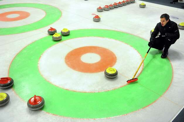 Derek Surka, of New Haven, watches his wife Charrissa Lin deliver a curling stone while practicing Saturday, Mar. 2, 2013 at the Nutmeg Curling Club in Bridgeport, Conn. The couple will be representing the Grand National Curling Club at the Mixed Nationals competition in Minnesota March 16th to the 24th. Photo: Autumn Driscoll / Connecticut Post