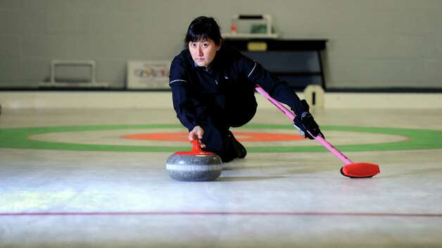 Charrissa Lin, of New Haven, delivers a curling stone while practicing Saturday, Mar. 2, 2013 at the Nutmeg Curling Club in Bridgeport, Conn.  Lin and husband Derek Surka will be representing the Grand National Curling Club at the Mixed Nationals competition in Minnesota March 16th to the 24th. Photo: Autumn Driscoll / Connecticut Post