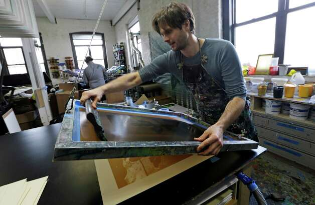 "Printmaker Karl LaRocca, 39, works on a silkscreen image from one of his Superstorm Sandy photographs for an art show benefiting storm victims inside his fourth floor studio overlooking Newtown Creek, a federal Superfund site, in New York, Wednesday, Feb. 20, 2013.  Larocca said, ""The rich people were all living farther away and used the creek for their industry. Now we've had this reversal where the waterfront is this desirable property and that's what they're cleaning up.""  (AP Photo/Kathy Willens) Photo: Kathy Willens"