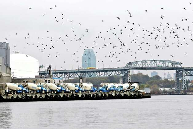 This Oct. 24, 2012 photo shows a cement factory on the banks of Newtown Creek in New York. Just across the East River from Manhattan, within sight of the United Nations and shimmering midtown skyscrapers, tens of millions of gallons of pollution are awaiting cleanup in a neighborhood where working-class families have lived for generations and wealthier ones are moving in. Newtown Creek straddling Brooklyn and Queens is home to a federal Superfund site the size of 55 football fields. (AP Photo/Mary Altaffer) Photo: Mary Altaffer