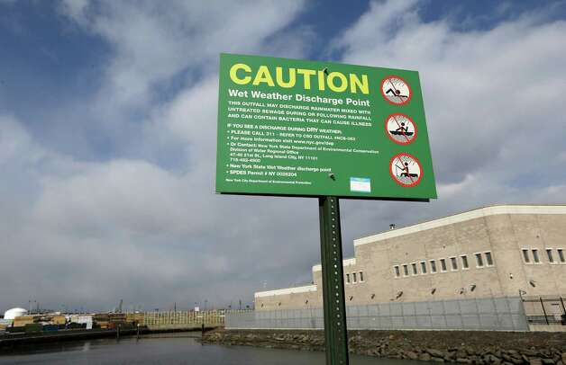 A sign posted on a bridge over a tributary of the Newtown Creek, a federal Superfund site, discourages swimming, boating and fishing during or after rainfall on the waterway, which is located in industrial neighborhoods of Brooklyn and Queens in New York, Wednesday, Feb. 20, 2013.  (AP Photo/Kathy Willens) Photo: Kathy Willens